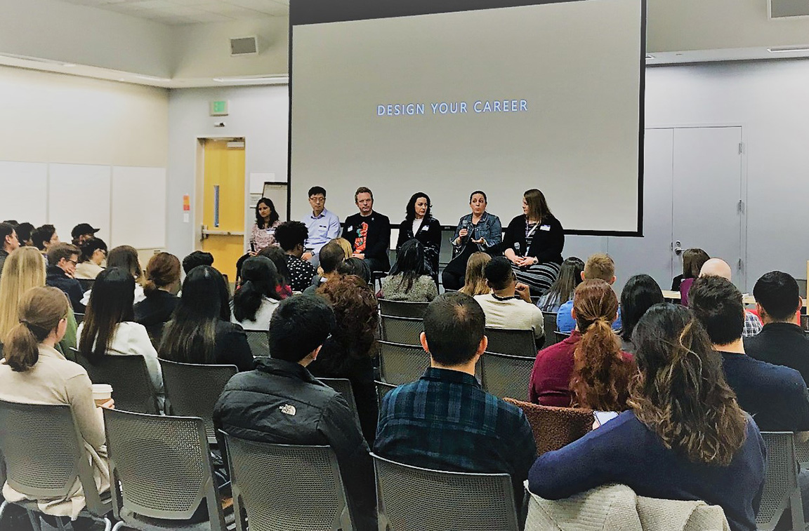 Six panelists speaking to a full room of students