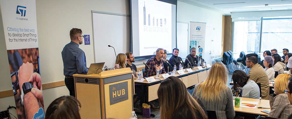 panelists at the front of the room in the HUB, with moderator Tyler Fox
