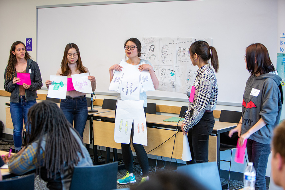 students presenting with mockup of clothing